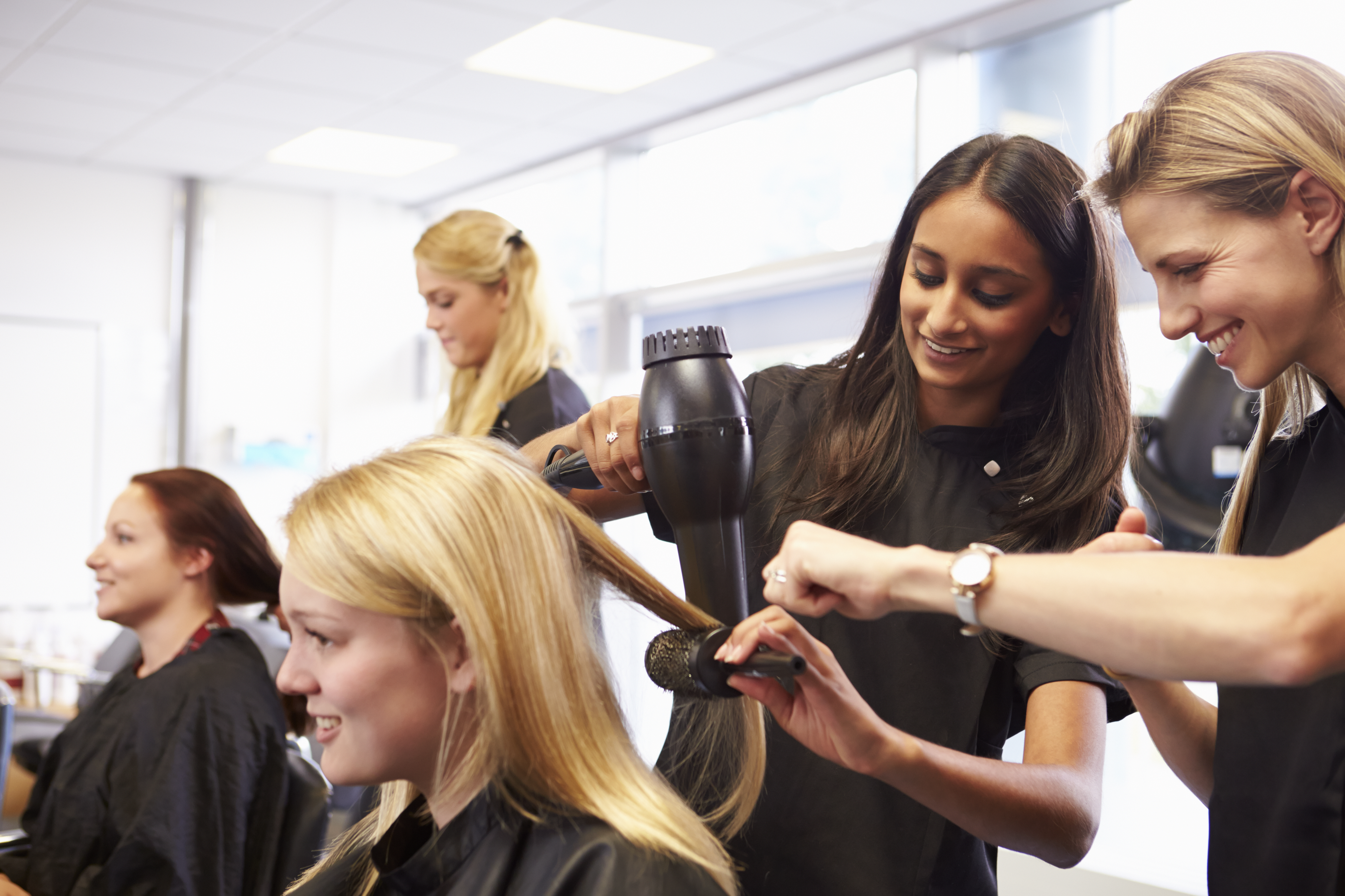 Apprentice hairdresser learning on the job