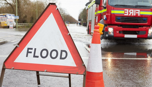 Flood warning sign in front of a fire engine