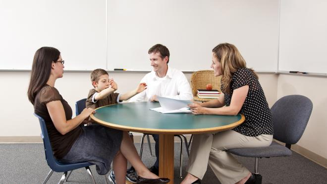 Teacher, social worker, foster carer and child sat around a table at PEP meeting