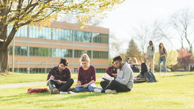 Students sitting on grass outside university campus